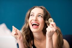 Happy woman with crypto coin at home