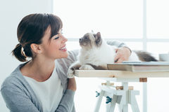 Happy woman cuddling her cat. Happy smiling woman at home cuddling and holding her lovely cat on a table, pets and togetherness concept Royalty Free Stock Photo