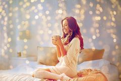 Happy woman with cup of coffee in bed at home Stock Photos