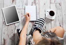Happy Woman with a cup of coffee, notepad and tablet Stock Photos