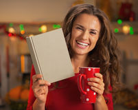 Happy woman with cup of hot chocolate reading book in kitchen Stock Image