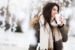 Happy woman with a cup of hot drink on  cold winter outdoors Royalty Free Stock Photo