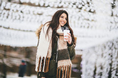 Happy woman with a cup of hot drink on  cold winter outdoors Royalty Free Stock Images