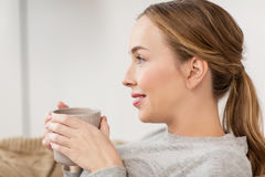 Happy woman with cup or mug drinking at home Royalty Free Stock Photography