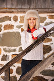 Happy woman with cup standing on stairs of cosy mountain house Stock Image