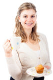 Happy woman with cup and sweet muffin Royalty Free Stock Image