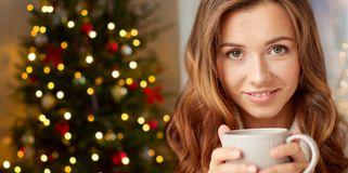 Happy woman with cup of tea or coffee on christmas royalty free stock photography