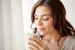Happy woman with cup of tea or coffee at home Stock Image