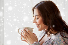 Happy woman with cup of tea or coffee at home. People, drinks, winter, christmas and bliss concept - happy young woman with cup of tea or coffee at home over Stock Photo