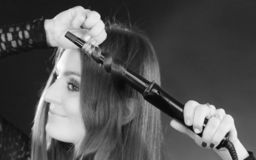 Happy woman curling her long brown hair stock photos