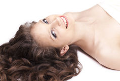 Happy woman with curly hair lying on the floor Stock Photography