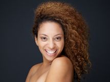 Happy woman with curly hair smiling on gray background Stock Images
