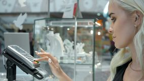 Happy woman customer in a jewellery shop pay card terminal contactless