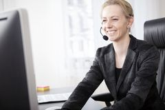 Happy Woman Customer Support Facing at her Monitor Stock Images
