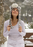 Happy Woman in Cute Animal Hat in Snow. A portrait of a pretty y9oung woman wearing a leopard hat outside on a snowy day Royalty Free Stock Image