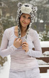 Happy Woman in Cute Animal Hat in Snow. A portrait of a pretty young woman wearing a leopard hat outside on a snowy day Royalty Free Stock Photography