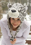 Happy Woman in Cute Animal Hat in Snow. A portrait of a pretty young woman wearing a leopard hat outside on a snowy day Royalty Free Stock Images