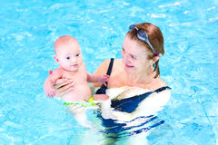 Happy woman and cute baby boy in swimming pool. Young mother and her little baby son relaxing in a swimming pool Royalty Free Stock Photos