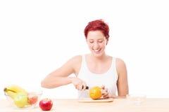 Happy woman cutting a orange Stock Photos