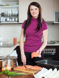 Happy woman cutting salmon for fish pie Stock Image