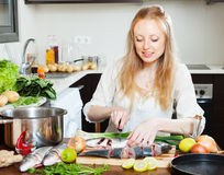 Happy woman cutting seabass fish Stock Images