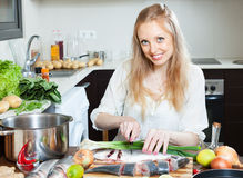 Happy woman cutting seabass Royalty Free Stock Image