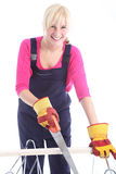 Happy woman cutting timber with a handsaw Royalty Free Stock Image