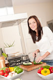Happy woman cutting zucchini in the kitchen Stock Photo