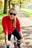 Happy woman cycling on bicycle, autumn Stock Photography