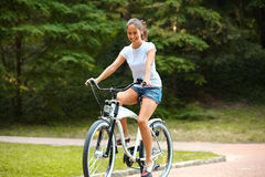 Happy Woman is Cycling in Summer Park Stock Photography