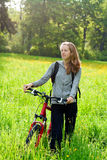 Happy woman cyclist with bike and backpack Stock Photos