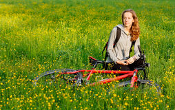 Happy woman cyclist with bike among the meadow Stock Photo