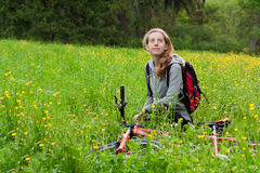 Happy woman cyclist with bike among the nature Royalty Free Stock Image