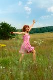 Happy woman dances on meadow Royalty Free Stock Image