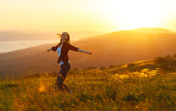 Happy woman  dances,  rejoices, laughs  on sunset in nature Stock Images