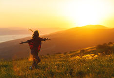 Happy woman  dances,  rejoices, laughs  on sunset in nature Royalty Free Stock Images