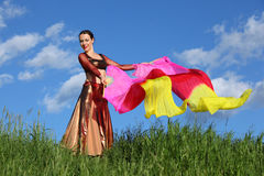 Happy woman dances with veil fans. Happy woman wearing beautiful suit dances with pink veil fans at green field under blue sky Stock Photography