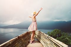 Happy woman dancing feeling free travelling the world raising arms to the sky stock photo