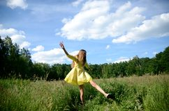 Happy woman dancing on the grass. Petite woman, wearing yellow dress, dancing in the meadow. Female model and nature stock photography