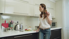 Happy woman dancing with mobile phone at modern kitchen stock footage