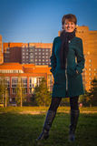 Happy woman in a dark coat standing outdoors autumn at sunset Royalty Free Stock Photography