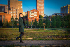 Happy woman in a dark coat walking outdoors autumn at sunset Royalty Free Stock Photos