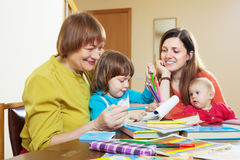 Happy woman  with daughter and grandchildren sketching  on paper Stock Photography