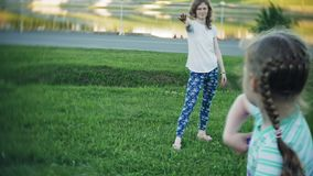 Happy woman and daughter playing in frisbee in park. 4k stock video footage
