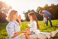 Happy woman with daughter playing on picnic. Happy women with daughter playing on picnic outdoor Stock Photo