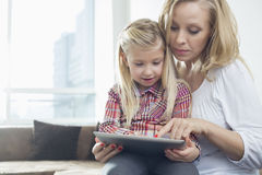Happy woman with daughter using digital tablet in living room Royalty Free Stock Photos