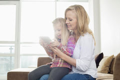 Happy woman with daughter using digital tablet in living room Stock Photo