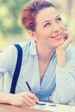 Happy woman daydreaming working outside corporate office on sunny day Royalty Free Stock Images