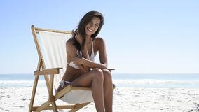 Happy woman on deckchair at beach. Beautiful woman sitting on a deck chair at the beach and looking at camera. Young tanned woman in white bikini enjoying the stock video footage