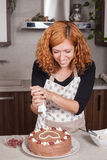 Happy woman decorating cake at home Stock Image